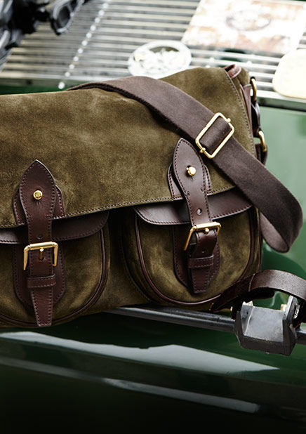 Olive suede cross-body bag with leather trim sits on trunk of green vintage sports car
