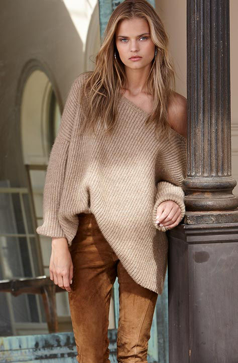 Woman wears an off-the-shoulder beige sweater & brown skinny pant