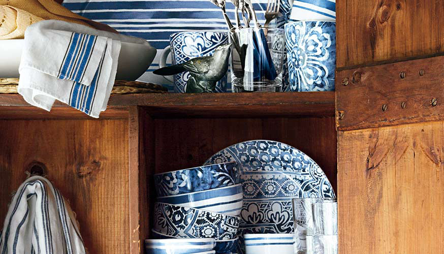 Rustic pine cabinet displays array of blue floral-patterned dishes and tea towels with blue stripes