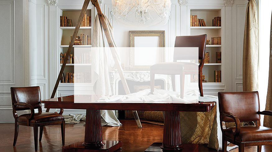 Dining table & leather chairs in room with elaborate wainscoting. Ladder with painter's drop cloths in background