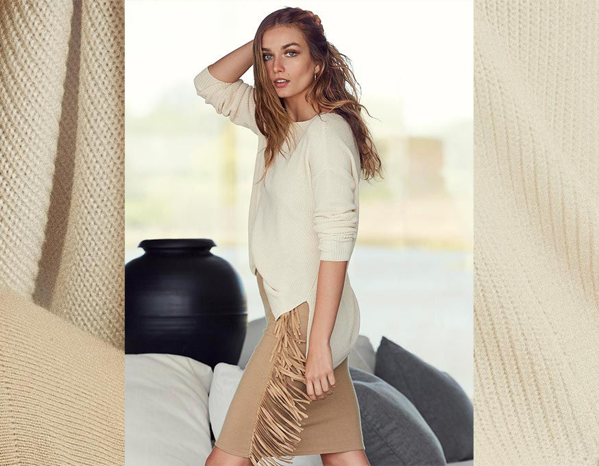 Woman walks through room wearing ivory sweater with uneven hem and fringed pencil skirt