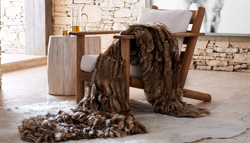 Shearling throw blanket drapes over a chair