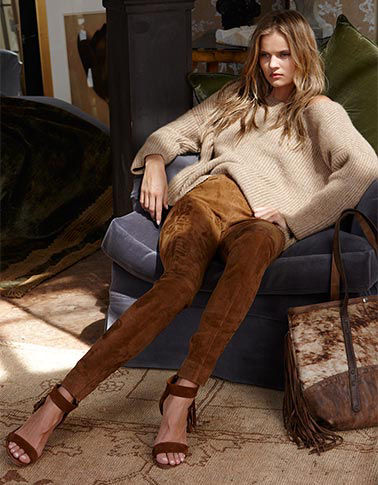 In a suede skinny pant & oversized sweater, woman reclines in chair