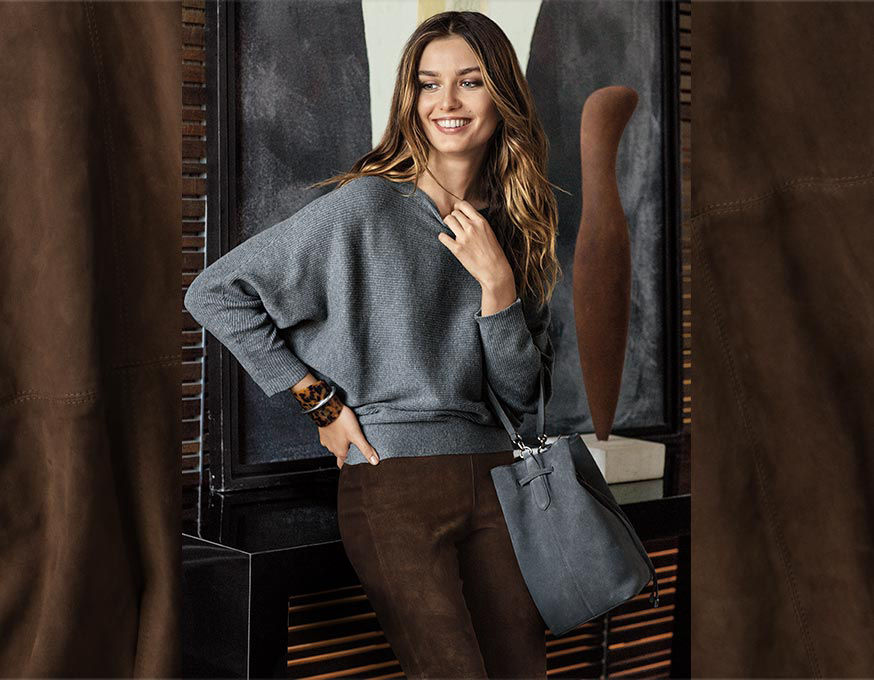Woman in grey dolman sweater & brown suede pant carries grey suede tote