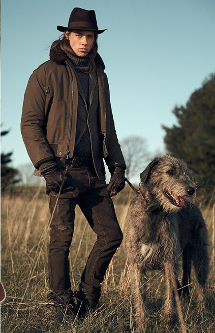 Man in brimmed hat, down bomber jacket & leather gloves walks dog