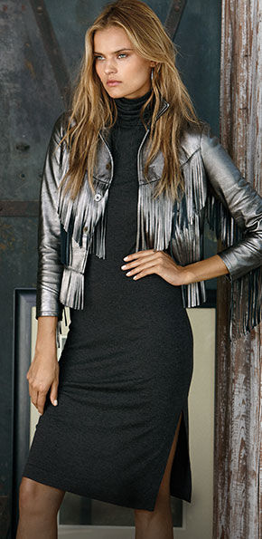 Woman layers silvery fringed leather jacket over grey turtleneck dress