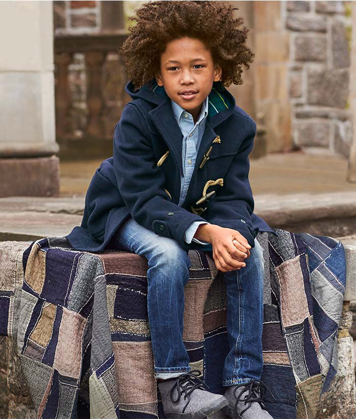 Boy wears navy hooded toggle coat with chambray shirt & jeans