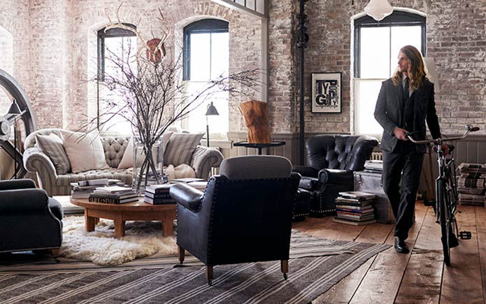 Man walks through loft with striped sofa, leather chairs and layered rugs