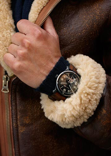 Close-up of man wearing wristwatch and shearling-trimmed jacket