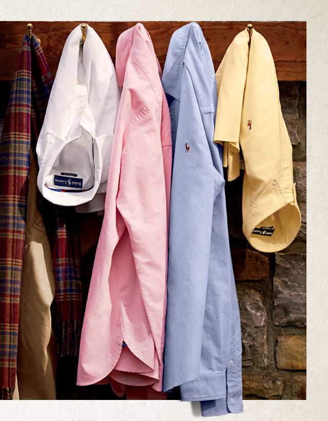 Oxford shirts in white, pink, blue & yellow hang from coat hooks