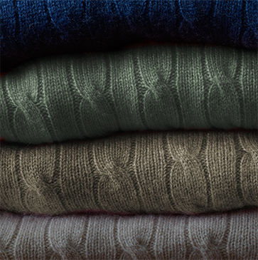 Stack of folded cable-knit sweaters in blue, light green, taupe & off-white