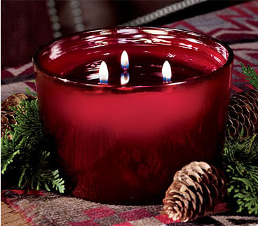 Three-wick candle in a red glass vessel