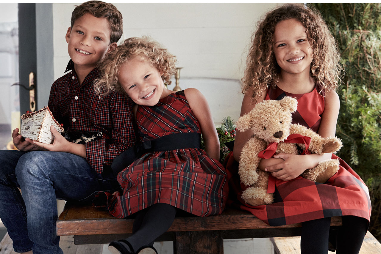 Boys wearing red plaid shirt sits with 2 girls wearing red plaid dresses