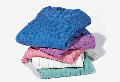 Stack of cable-knit V-neck sweaters in blue, purple, pink, white, and green.