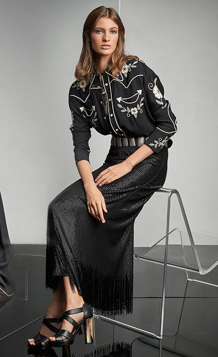 Woman pairs black-and-white Western shirt with shimmering fringed skirt