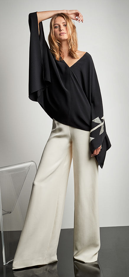 Woman pairs flowing charcoal tunic with cream-toned wide-leg pant